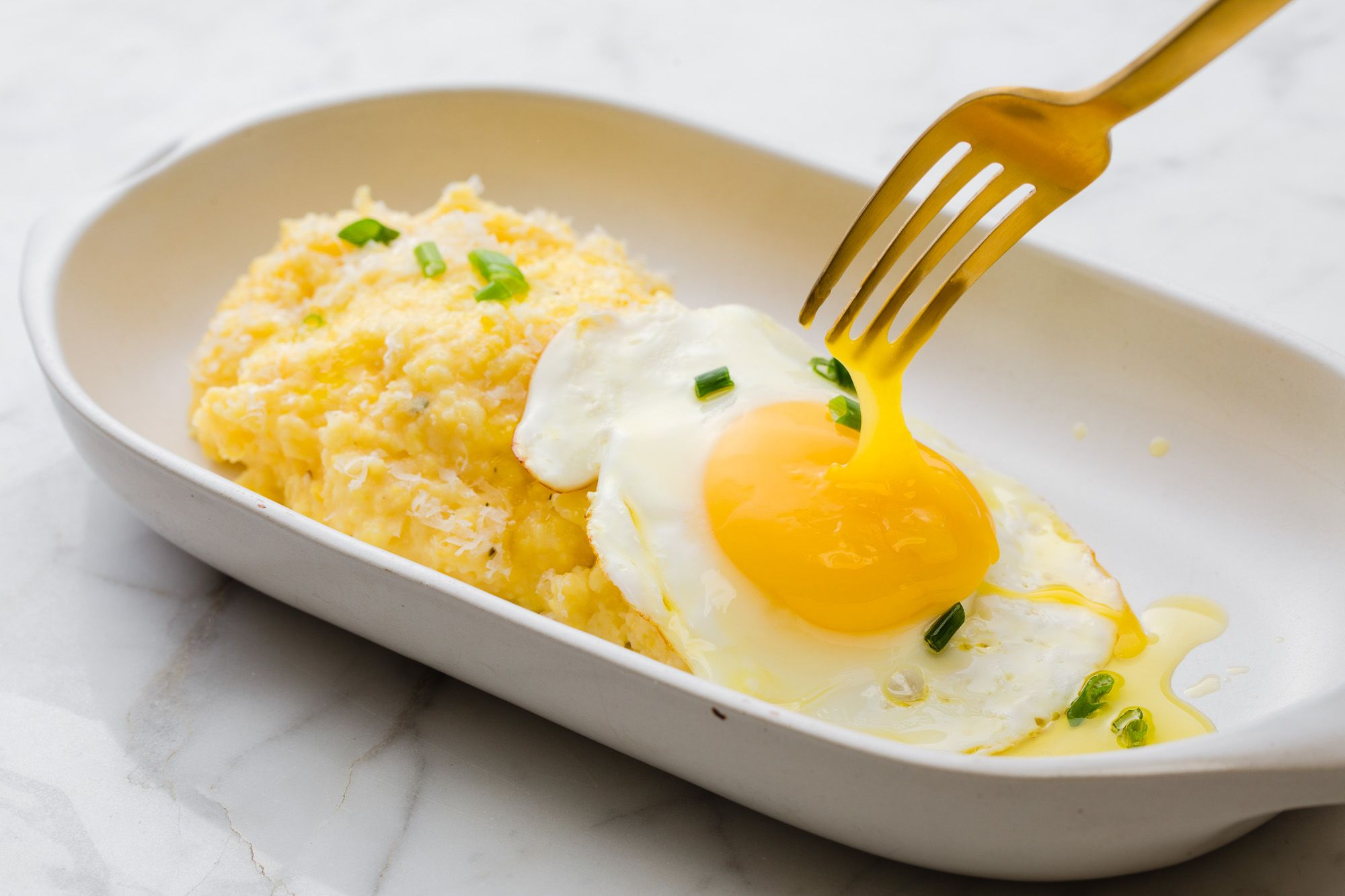 A plate of fried eggs over polenta cooked with Bertolli extra virgin olive oil. Easy Cooking recipes with olive oil. Bertolli