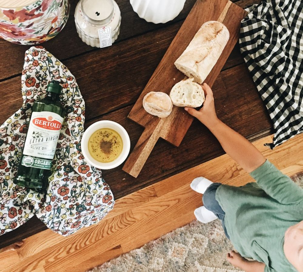Cooking table with a bottle of Bertolli extra virgin olive oil, bread and a cutting board. Best olive oil brands. Bertolli