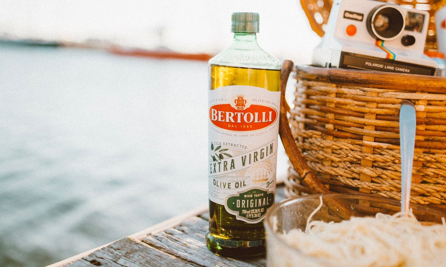 A glass bottle with Bertolli Olive Oil with Italian pasta represent Italian food recipies and cooking with Bertolli extra virgin olive oil.