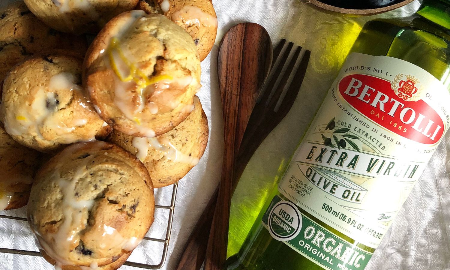 A green glass bottle with Bertolli Olive Oil with and fresh baked cookies represent easy cooking recipies. Olive Oil nutrition.