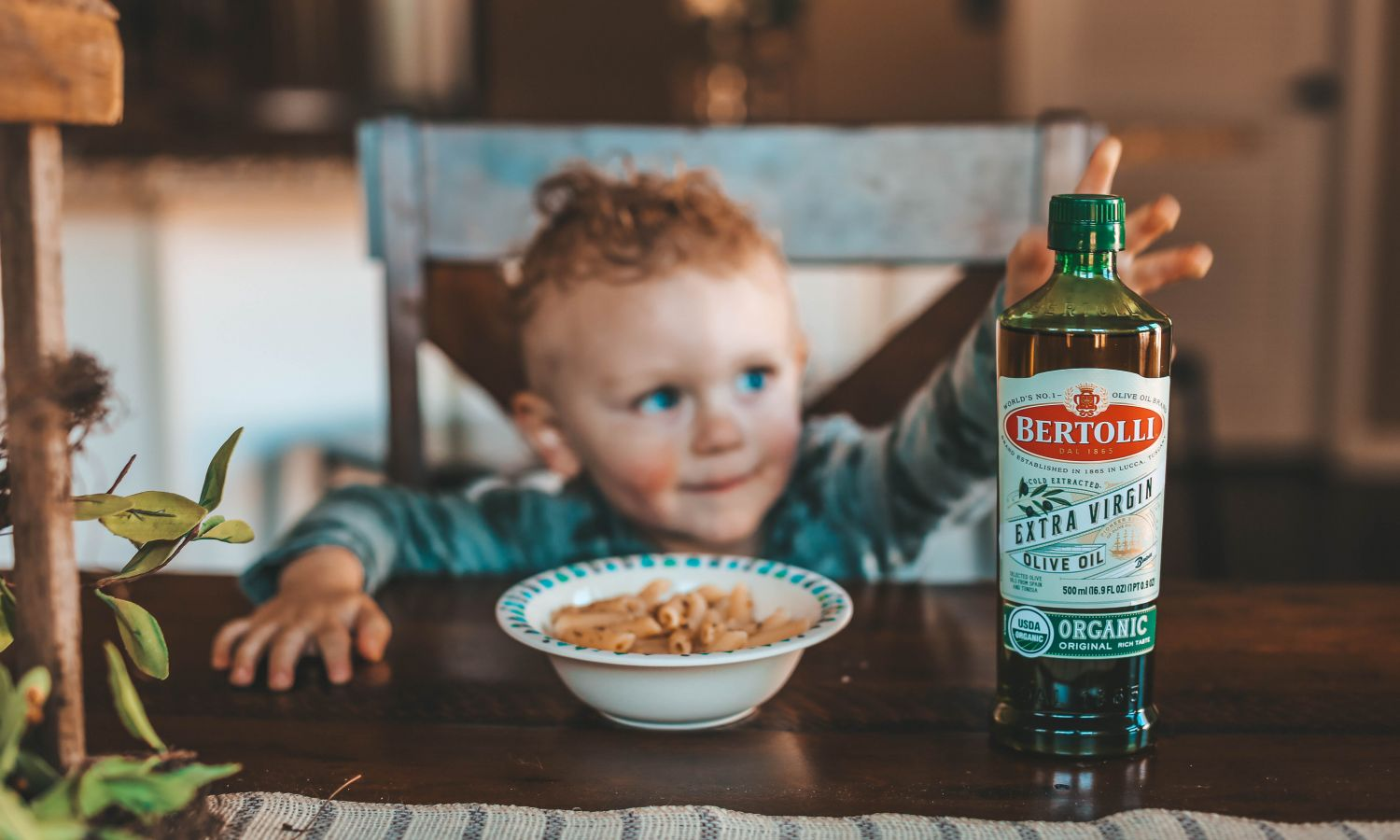 Bertolli Extra Virgin Olive Oil Bottle, a bowl of pasta, a child sitting in a chair representing Quality extra virgin olive oil