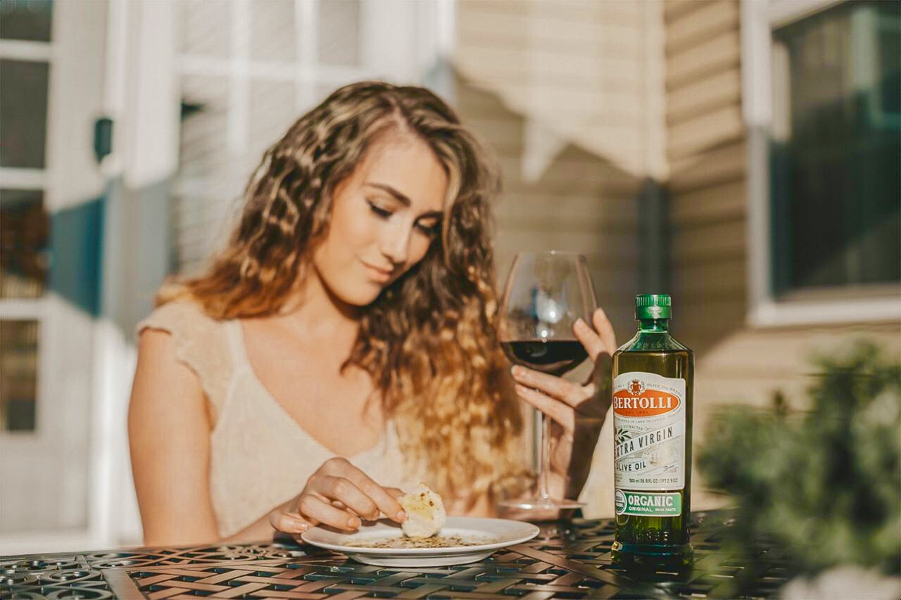 A girl with a glass of wine and Bertolli Olive Oil on a table